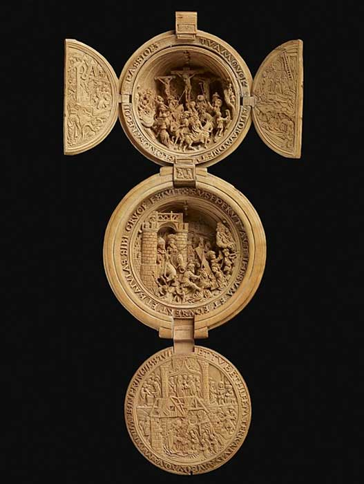 A boxwood carving in the form of a rosary bead or prayer-nut. On the outside of the doors, the Virgin in the Temple (left), Marriage of the Virgin (right); inside the same doors, Moses and the Brazen Serpent (left) and the Deposition (right). Inside the upper half of the nut, the Crucifixion. The lower half of the prayer-nut is shut with one hinged flap which is carved on both sides: on the front, The Annunciation with the words spoken by the Virgin and by Gabriel within the scene as scrolls; on the other side, The Nativity, with smaller scenes of the Circumcision, Presentation in the Temple, and Christ among the doctors. Inside the lower half of the prayer-nut, is the Bearing of the Cross. On the outside of both halves, Gothic tracery and flower-heads.