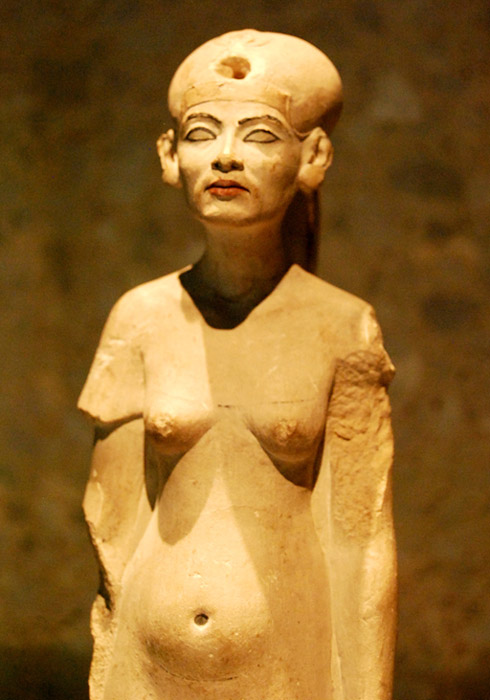 Far from being the iconic beauty depicted in her famous bust, Nefertiti is portrayed in a rather unflattering manner in this statuette from the latter-half of the Amarna era. Neues Museum, Berlin.