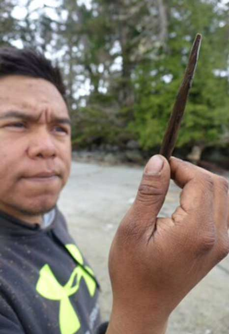 Josh Vickers, of the Heiltsuk First Nation and the archeological team, holds up a rare 6,500-year-old carved wooden bi-point.