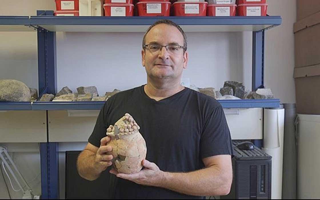 Haifa University Prof. Danny Rosenberg holds the 7,200-year-old model clay grain silo found at Tel Tsaf in the Jordan Valley.