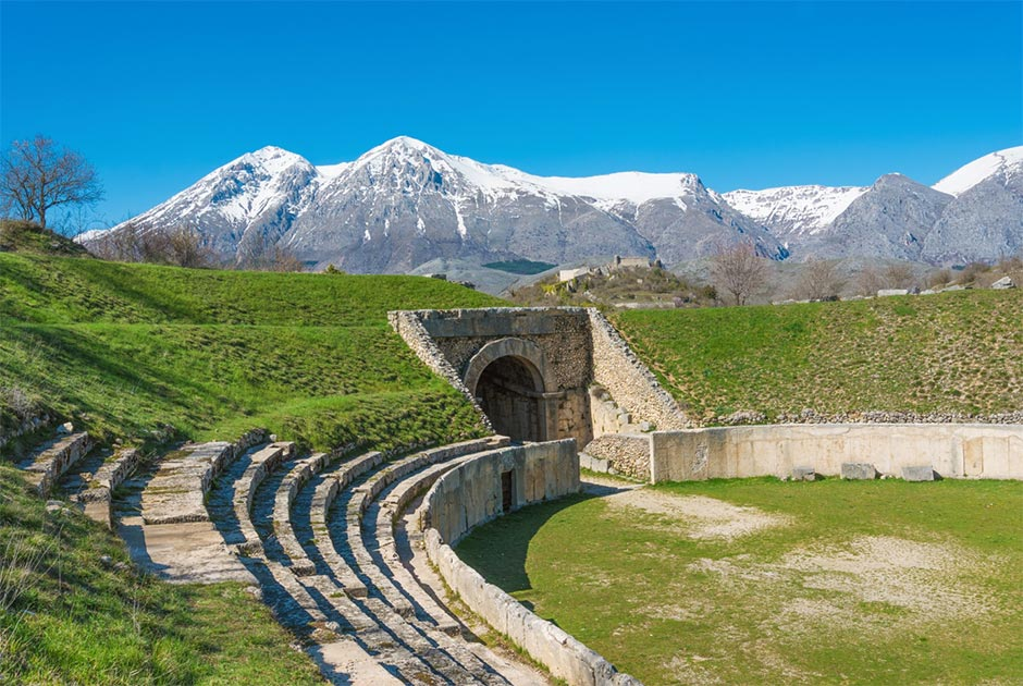 Alba Fucens, Roman archaeological site with amphitheater. Monte Velino mountain with snow, Abruzzo region, central Italy   Source: ValerioMei / Adobe Stock
