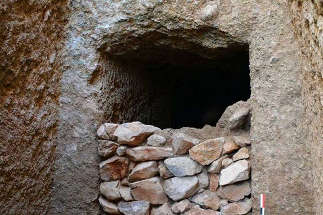 Detail of the Mycenaean-era tomb's façade and the dry-stone masonry that sealed the entrance.