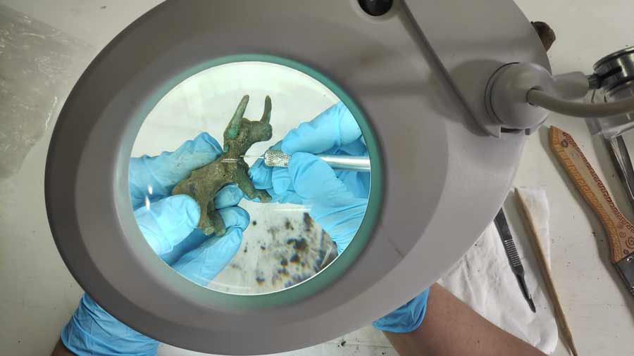 Conservators clean up the bronze bull idol uncovered in Olympia.	Source: Greek Ministry of Culture and Sports