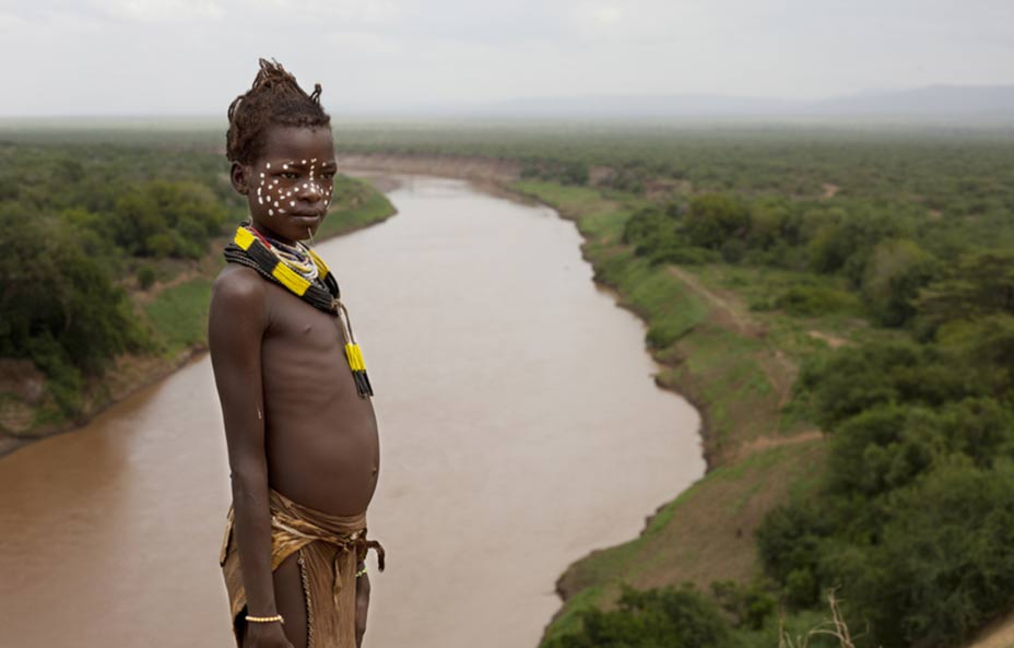 Child from the Karo tribe with the Valley of the Omo River behind.