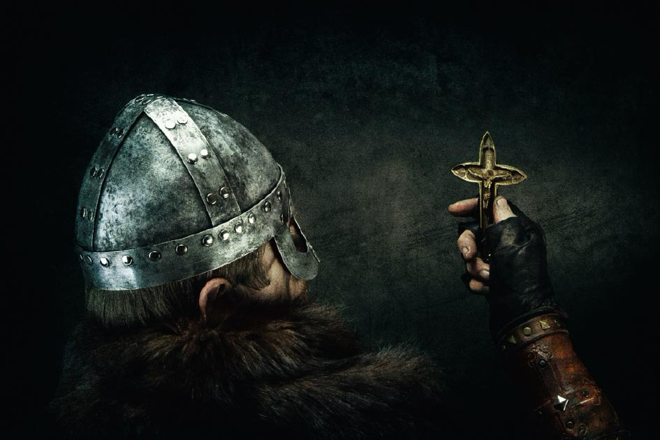 Viking holding Christian cross. Credit: Warpedgalerie / Adobe Stock