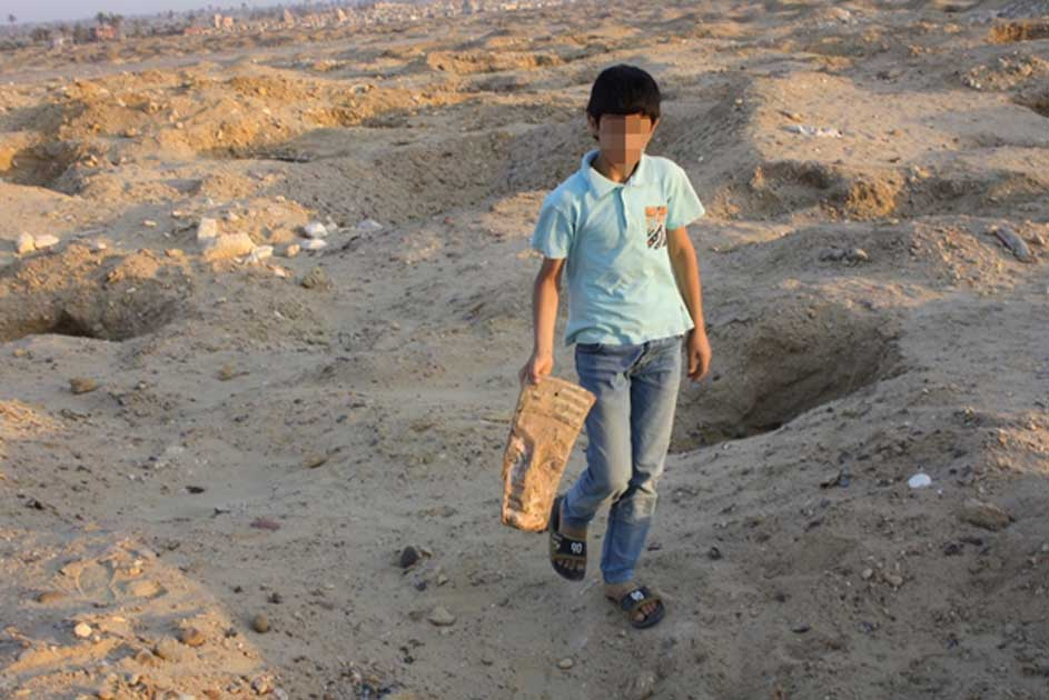 A child carrying an artifact at the cemetery.