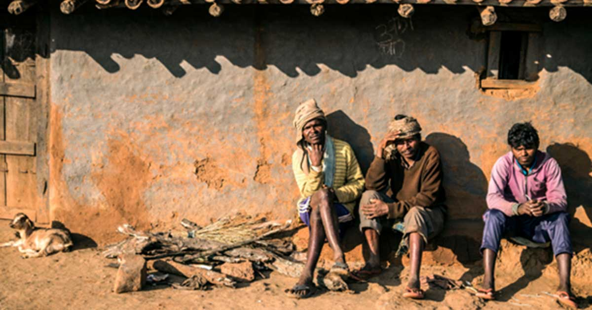 A group of Asur men outside a traditional hut in Polpol Path.