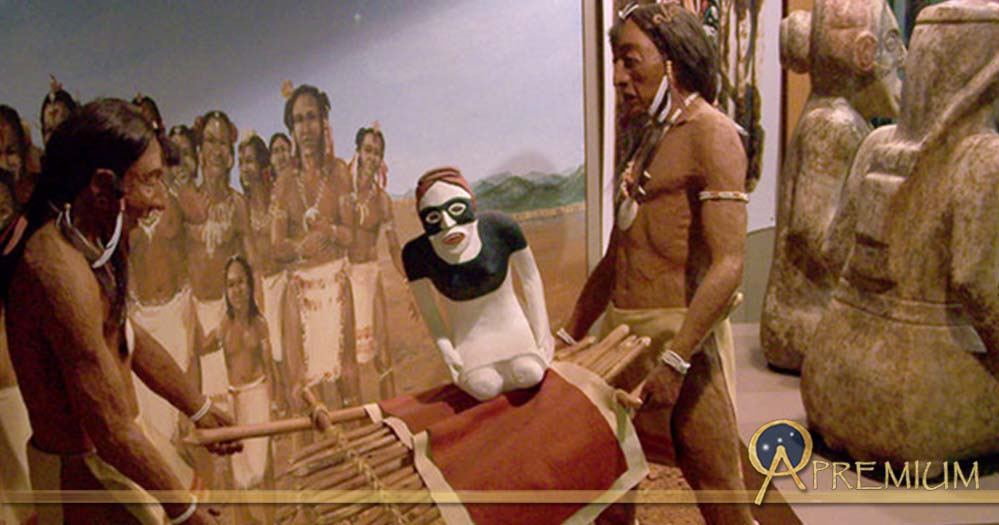A diorama at the Etowah Mounds showing two stone effigies being ritually buried, next to the actual statues, seen from the rear