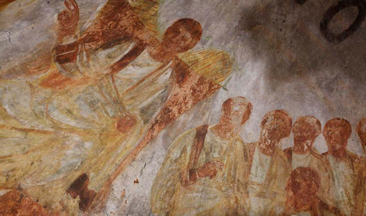 In this fresco, Jesus is shown seated on a throne with his disciples at hand. The painting is in the Catacombs of St. Domitilla in Rome, which have been newly restored.