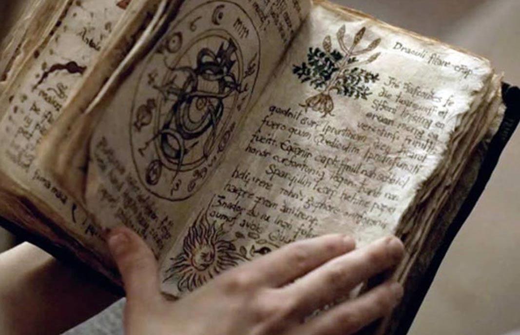 Person holding an ancient grimoire
