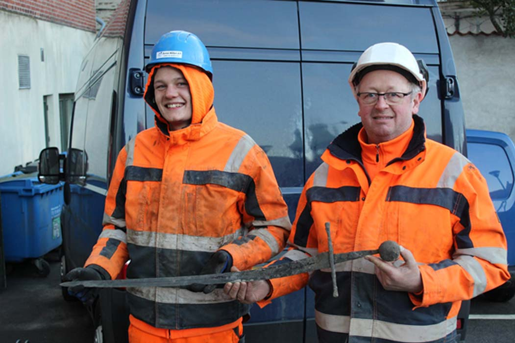Plumber Jannick Vestergaard and operator Henning Nøhr unearth a medieval sword on a Danish Street, February 5th.