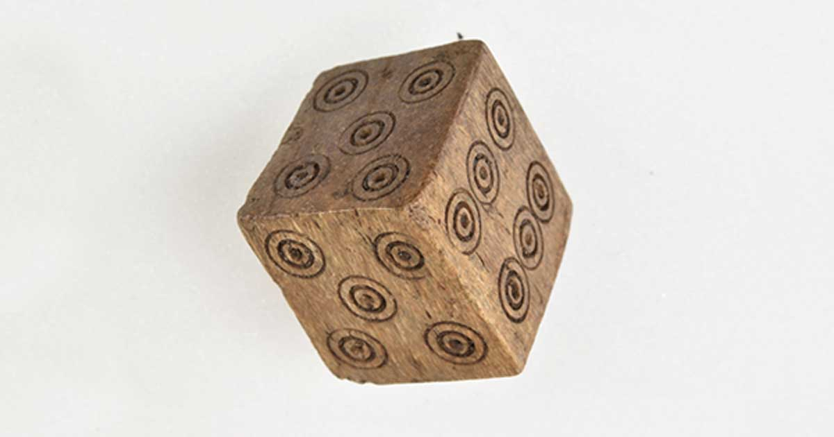 This Medieval dice has two 4's and two 5's but no 1 or 2. Archaeologists believe that it was likely used to cheat while gambling. This photo shows the two 5's.