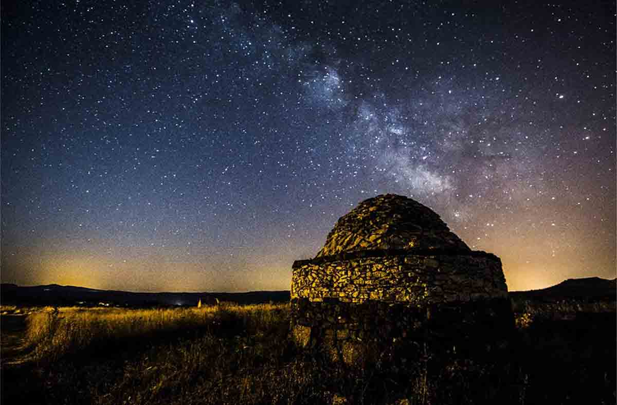 A view of a reconstructed hut at the Nuraghe Antine site at night.