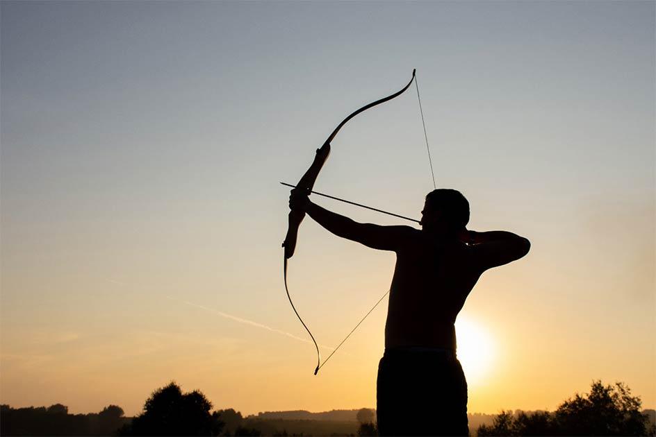 Man using bow and arrow. Credit: Oksana Volina / Adobe Stock