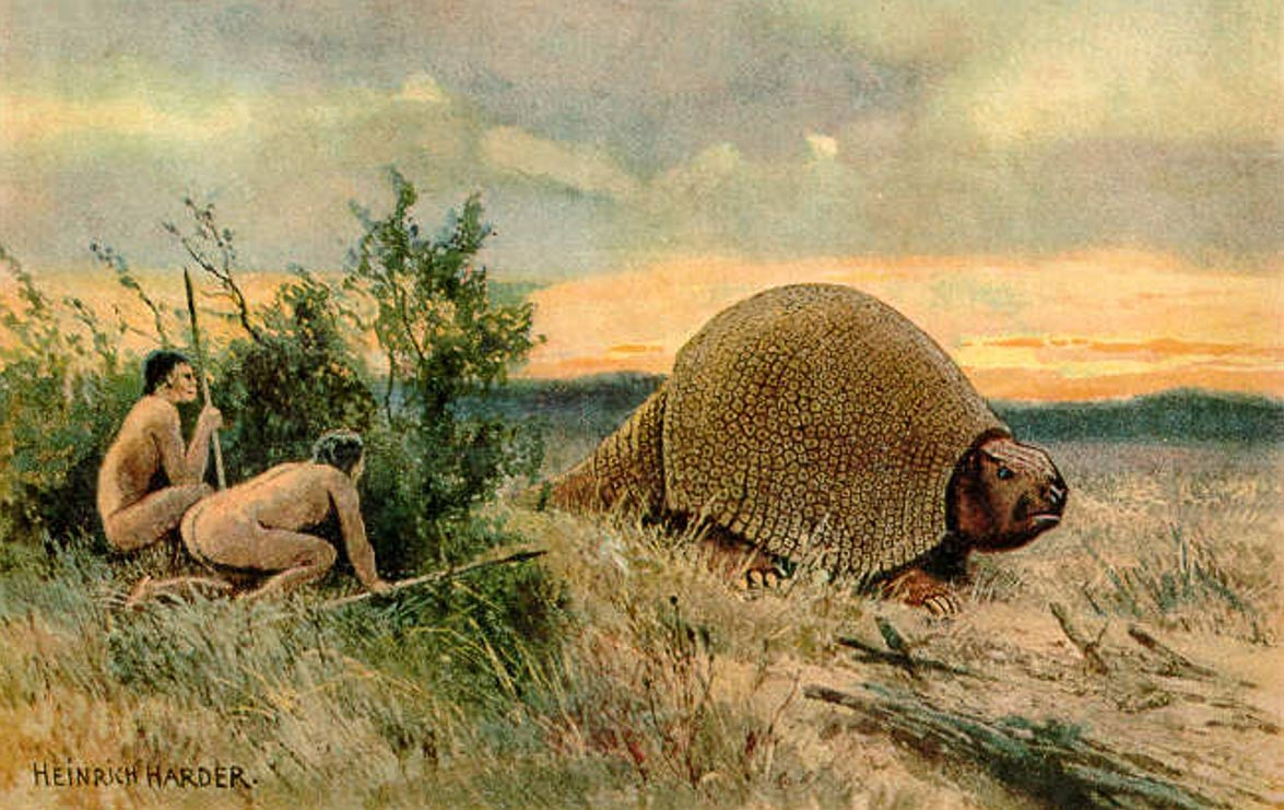 Paleolithic man (Paleoindians) hunting a glyptodon – ancient ancestor to the armadillo. (Illustration 1920) Did these societies use poison to bring down their prey?