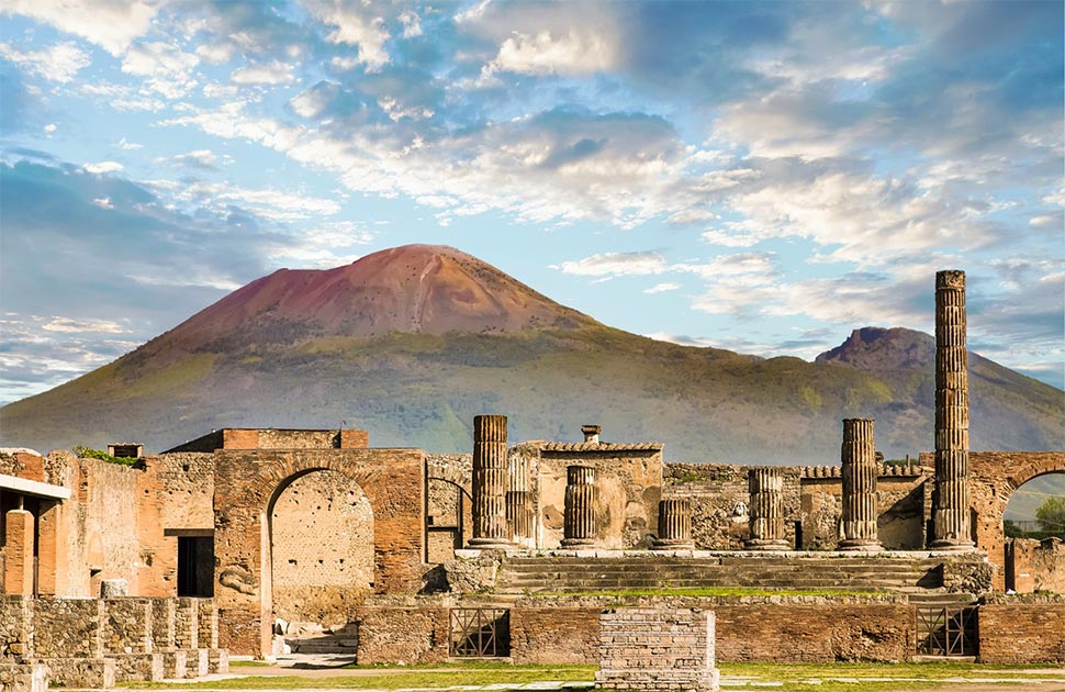 """Archaeologists have unearthed """"recycling sites"""" outside the walls of ancient Pompeii, showing the Pompeiians once recycled trash in an a very effective manner. Pictured: shot of the ruins with Mount Vesuvius in the background.      Source: dbvirago / Adobe stock"""