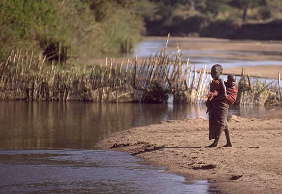 Child standing on the edge of a river