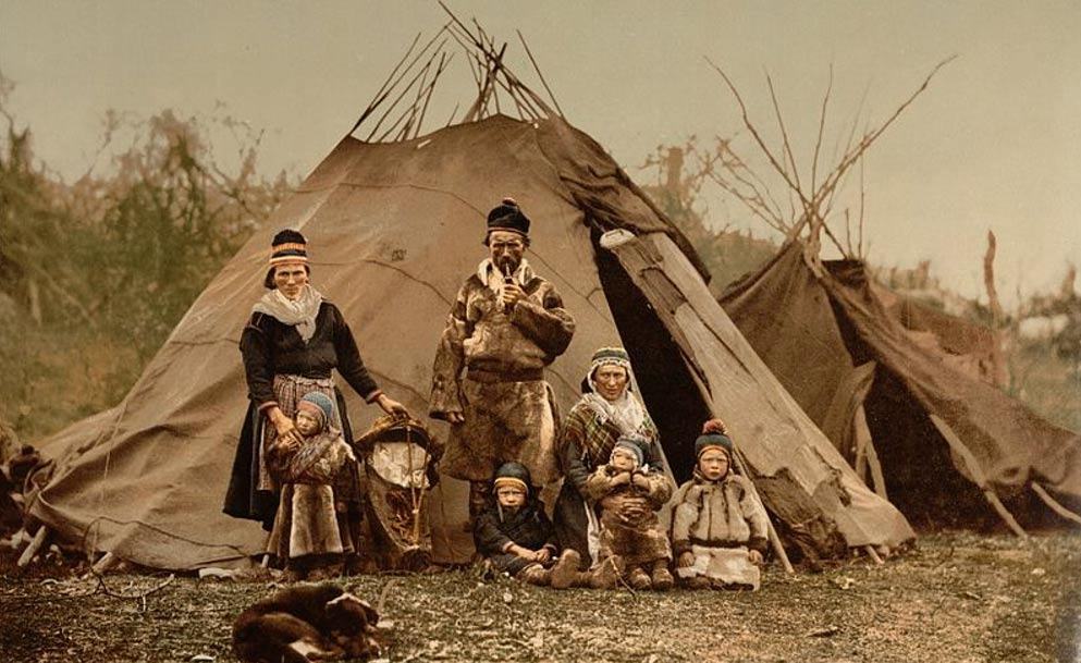 A Sámi family  in front of goahti and lavvu housing, early 1900s, Norway
