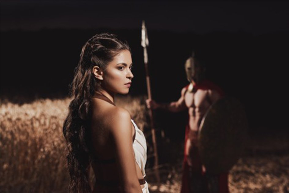 Spartan woman in foreground with her warrior husband in the background.   Source: serhiibobyk / Adobe stock