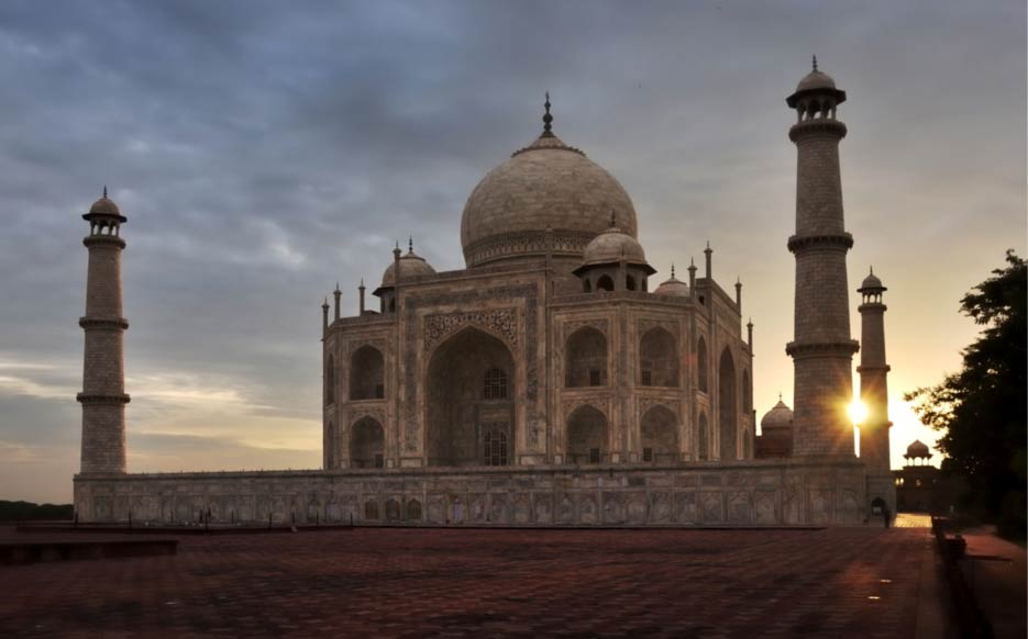 The sun rises behind the Taj Mahal
