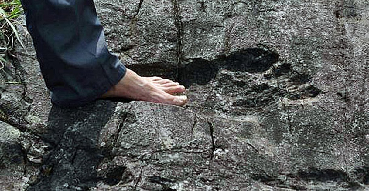 A man stands in what appears to be a giant footprint in bedrock in Pingyin China