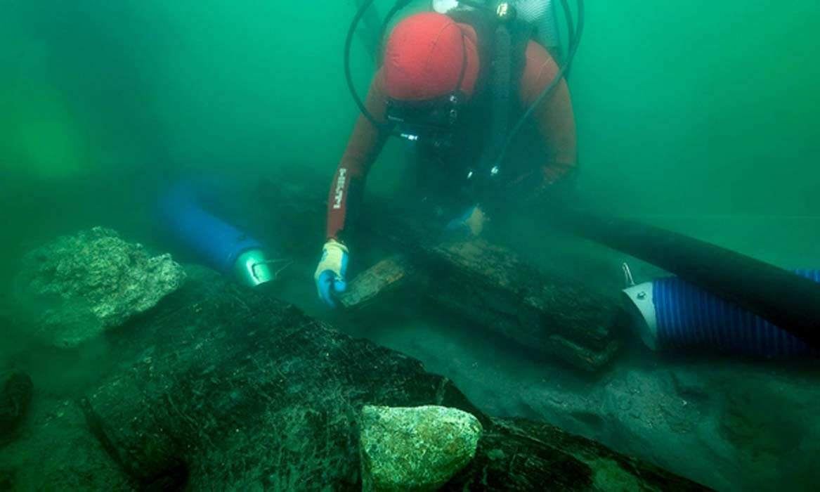 An archaeologist inspects the keel of a shipwreck discovered in the waters around the sunken port-city of Thonis-Heracleion where marine archaeologists found new Egyptian ship.