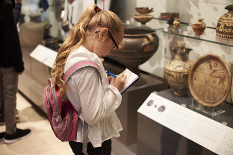 Student studying artifacts in a museum. Credit: Monkey Business / Adobe Stock