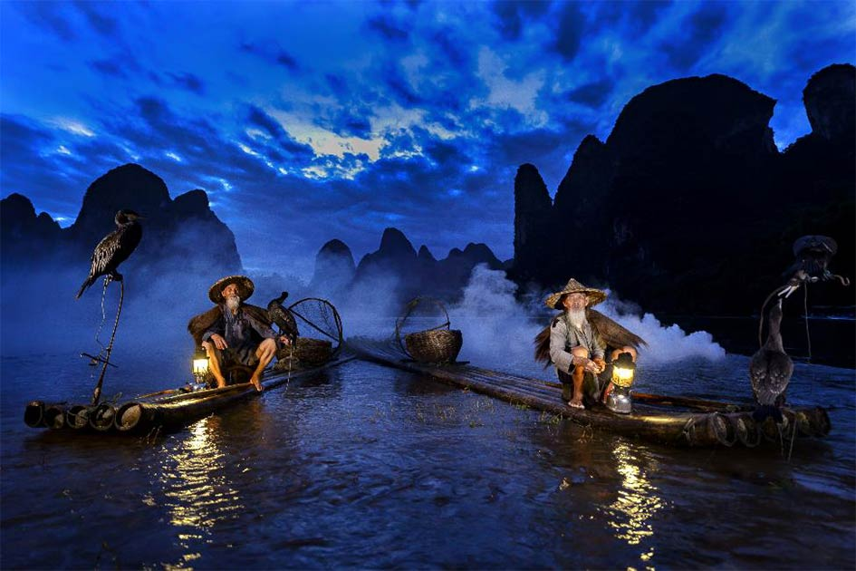Cormorant fishing on the Li River during the blue hour of dawn, Guangxi, China. (stveak /Adobe Stock)