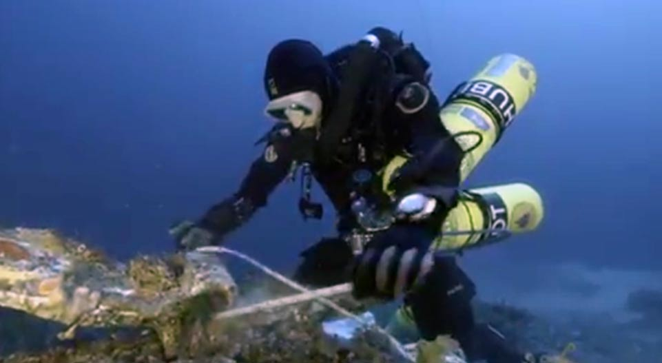 A diver securing an artifact found on the sea floor