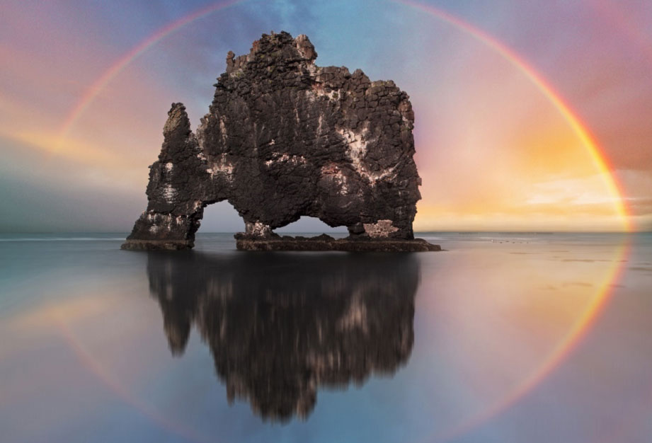 Colorful Rainbow over an ocean rock in Iceland.
