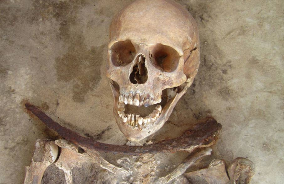 30-39 year old female's remains with iron sickle placed across neck