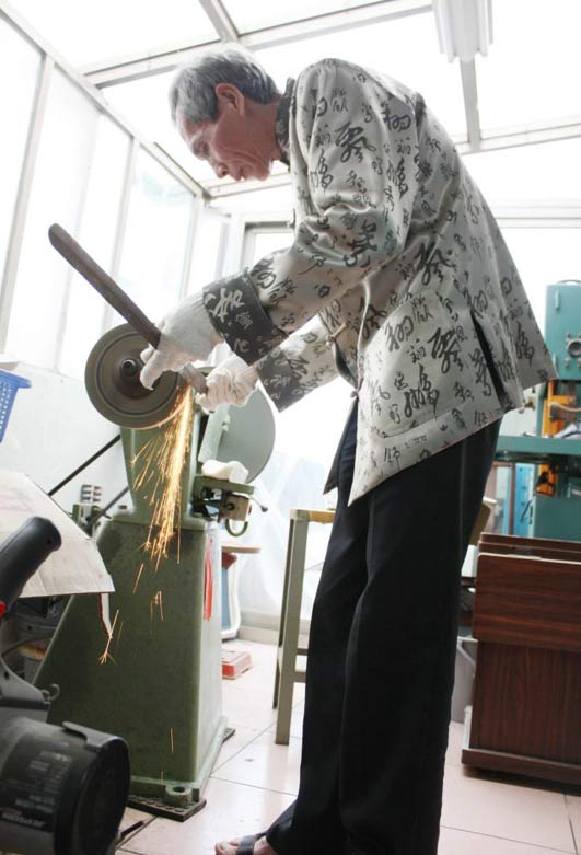 Chen demonstrates how he grinds the steel bars into swords in his workshop. It is a long and arduous process. The slightest of errors can ruin the blade, which would otherwise fetch thousands of dollars.