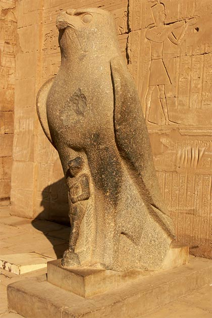 Closeup of the god Horus statue in front of the pylon temple entranceway (Walwyn / Flickr)