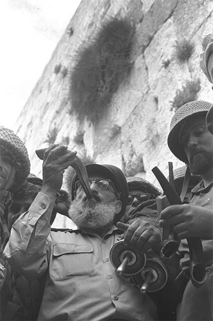 On June 7, 1967, during the Six Day War, Army Chief Chaplain Rabbi Shlomo Goren, surrounded by IDF soldiers, blows the shofar horn in front of the Western Wall in Jerusalem, declaring the Jewish return to the Temple Mount after a two-millennia-long absence. (Government Press Office (Israel)/CC BY SA 4.0)