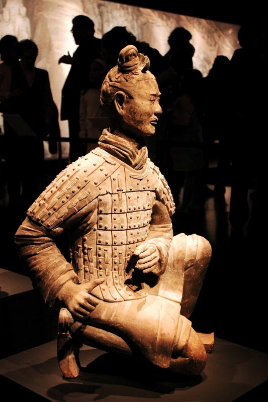 A kneeling terra cotta archer, with hands posed to hold a bow.