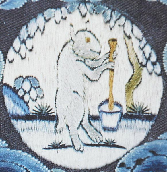 A medallion on an 18th-century embroidered Chinese emperor's imperial robe showing the White Hare of the Moon, at the foot of a cassia tree, making an elixir of immortality.