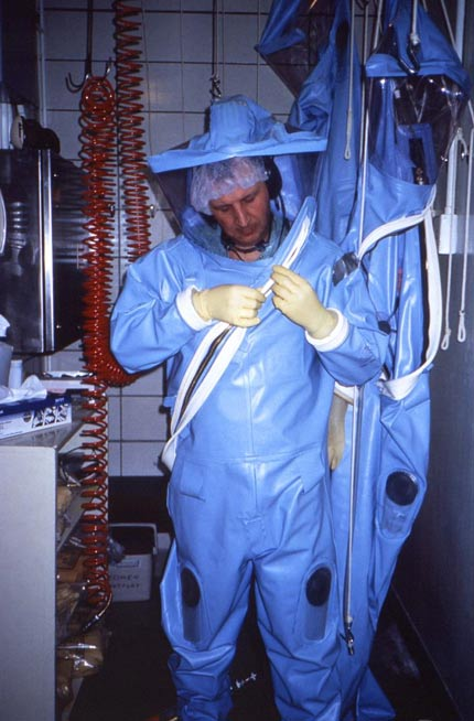CDC technician dons an older-model positive-pressure suit before entering one of the CDC's earlier maximum containment labs.