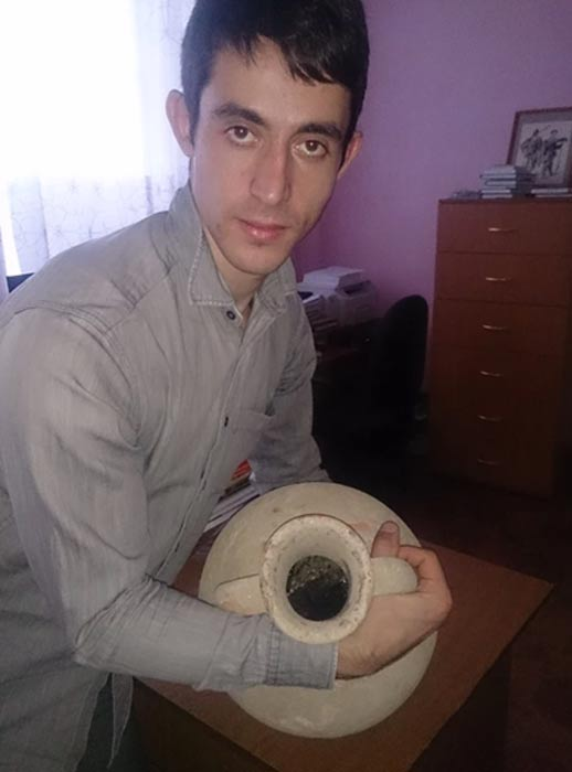 One of the researchers holding the Greek amphora.