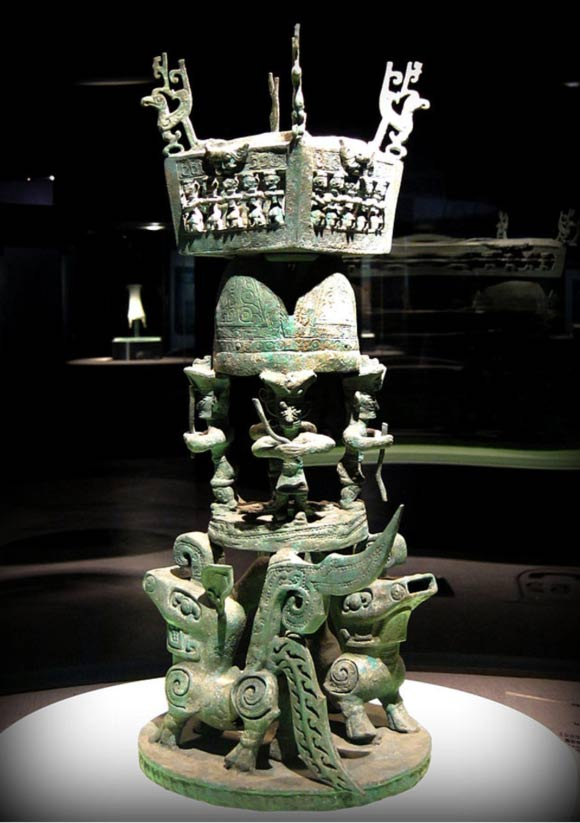 A sacrificial altar with several four-legged animals at the base to support a few bronze figures closely resembling the large face masks