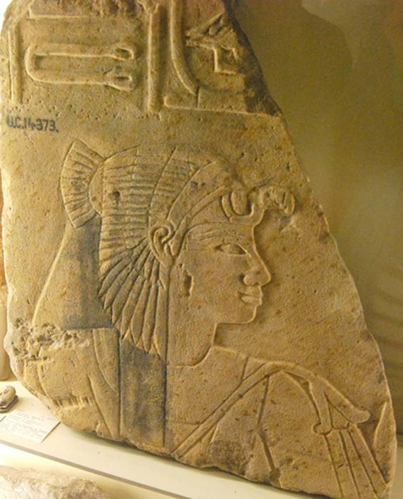 Detail from a sandstone block fragment from the mortuary temple of Amenhotep III depicts Princess Sitamun wearing a vulture headdress and holding a floral scepter. Petrie Museum, London.