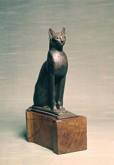 This seated cat has golden earrings, a golden scarab inlaid on the forehead, and a necklace with a pendant in low relief
