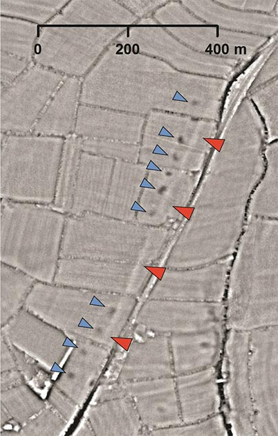 A section of a probable Roman road. The road's 'agger' – the raised metaled surface – shows as a straight pale line (red arrows). A line of quarry pits show as black spots (blue arrows) and these would have been possibly used to gather material for the road . (University of Exeter)