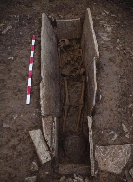 One of the skeletons in the stone coffin structure with a pot (at bottom of the shot) unearthed at the Roman burial site. (Wessex Archaeology)