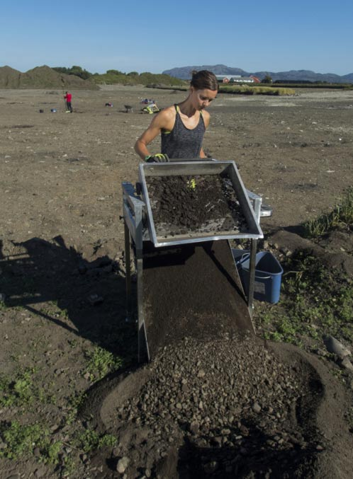 Synne H. Rostad operates a standing sieve to sift out smaller bones and objects from the dirt.