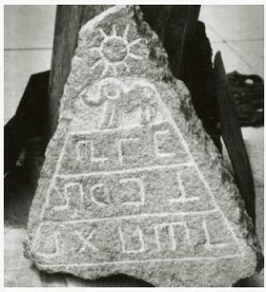 The stone tablet with the sun figure, a pyramid, and an elephant.