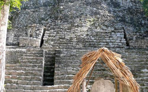 """Front view of the pyramid structure known as """"La Iglesia"""" in the Group B, or Cobá Group, complex. Stela 11 is in the foreground at the base of the pyramid's steps, under the thatched roofing. (Public Domain)"""