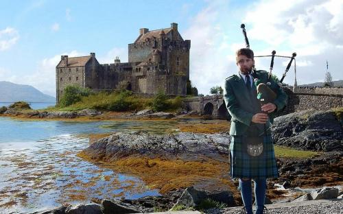 Piper on shore near castle (CC BY-SA 4.0)