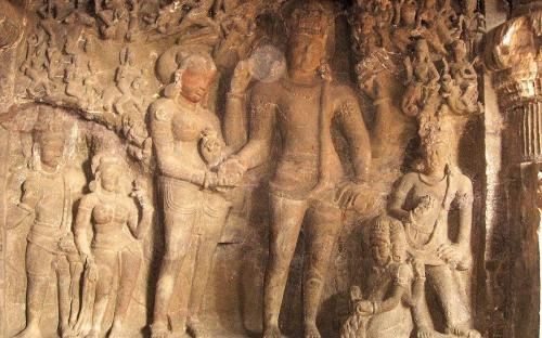 Wall carvings – A scene depicting the wedding of Shiva (four armed figure, right) and Parvati (two armed, left). (CC BY-SA 3.0)