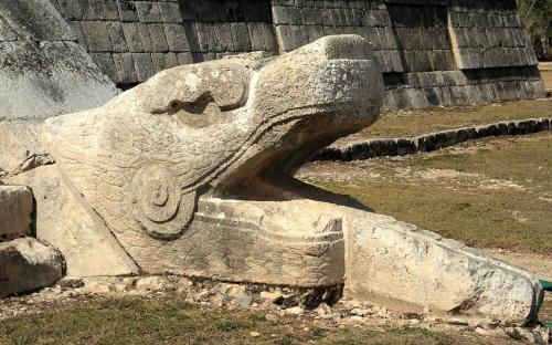 A feathered serpent sculpture at the base of one of the stairways of El Castillo. (CC BY 2.0)