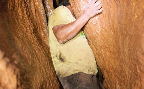Squizing through small tunnel - Tayos Caves